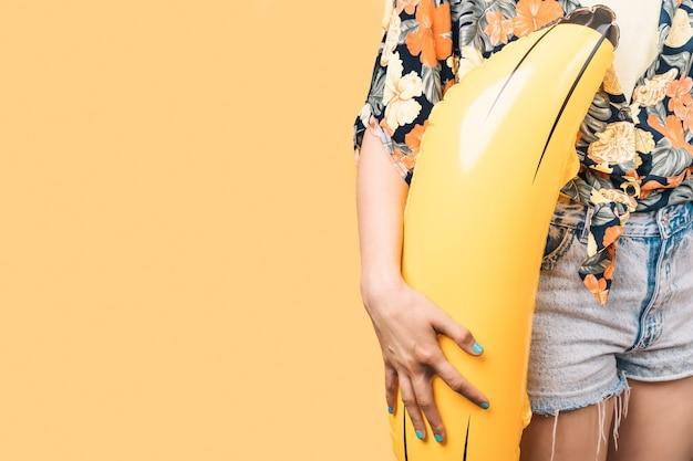 Kobieta w letnich ubraniach trzymająca nadmuchiwanego banana