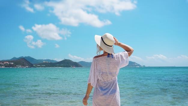 Kobieta w letnie wakacje w słomkowym kapeluszu i plażowej sukience, ciesząc się widokiem na ocean