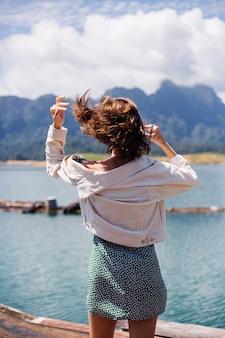 Kobieta w letniej sukience i kurtce podróżuje turystycznie po tajlandii, park narodowy khao sok, niesamowity widok na łodzie i jezioro.