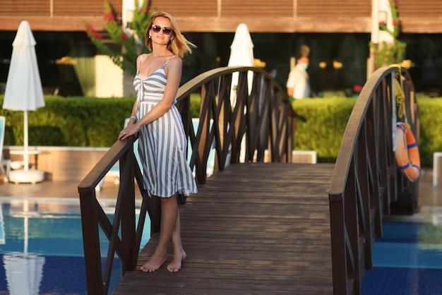 Kobieta w letniej sukience stoi obok małego mostu na terenie hotelu