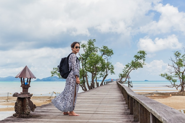 Kobieta w letniej sukience stojącej na drewnianym moście z spokojnym krajobrazem.