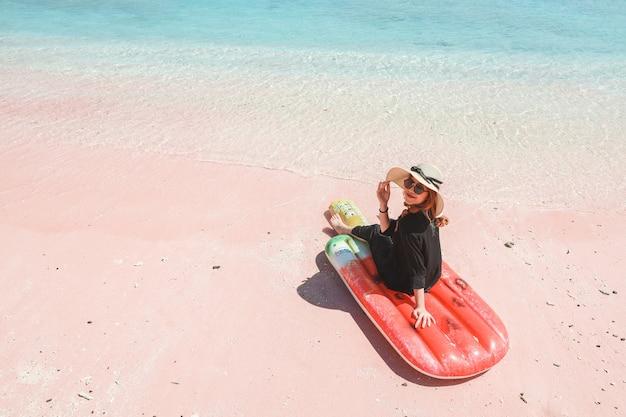 Kobieta w letnim kapeluszu i okularach przeciwsłonecznych w aparacie, siedząc na dmuchanym materacu na różowej piaszczystej plaży