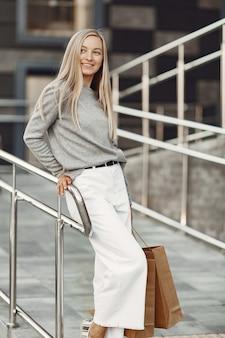 Kobieta w letnim mieście. pani z brązowymi torbami. kobieta w szarym swetrze.