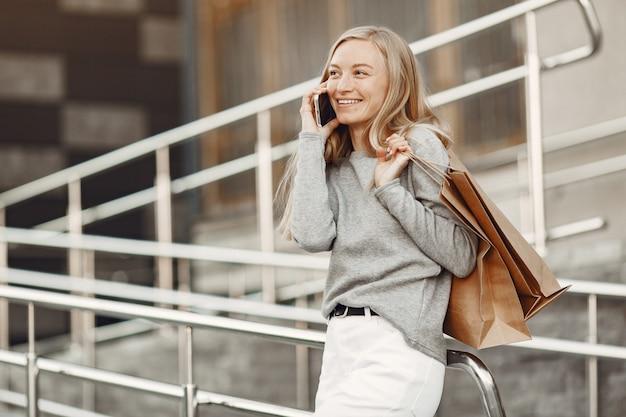 Kobieta w letnim mieście. pani z telefonem komórkowym. kobieta w szarym swetrze.