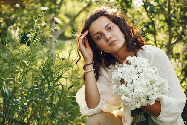 Kobieta w letnim polu. brunetka w białej koszuli.
