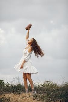 Kobieta w letnim polu. brunetka w białej sukni. dziewczyna z głośnikiem muzyki.