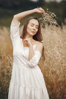 Kobieta w letnim polu. brunetka w białej sukni.