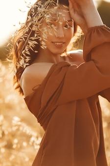 Kobieta w letnim polu. brunetka w brązowym swetrze.