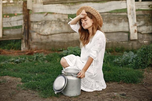 Kobieta w letnim polu. dziewczyna w białej sukni. kobieta z beczką mleka.