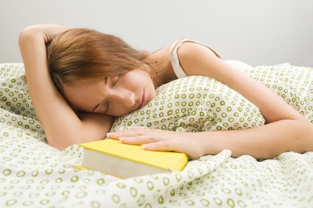 Kobieta w łóżku spać z książką