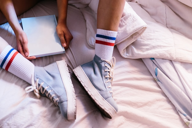 Kobieta w łóżku z niebieskim kapcie w domu zaczyna czytać książkę