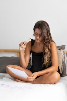 Kobieta w łóżku z piórem i papierami
