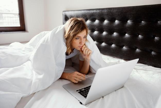 Kobieta w łóżku za pomocą laptopa