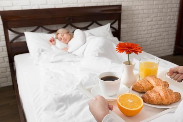 Kobieta w łóżku zaskoczona kwiatami i śniadaniem