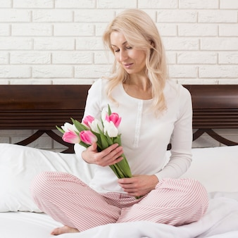 Kobieta w łóżku zaskoczony kwiatami