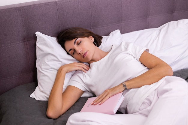 Kobieta w łóżku zasnęła trzymając papierowy notatnik notatnik znak 2021