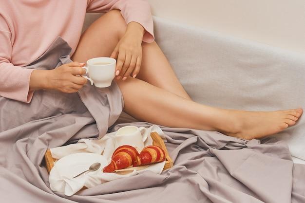 Kobieta w łóżku ze śniadaniem i filiżanką kawy