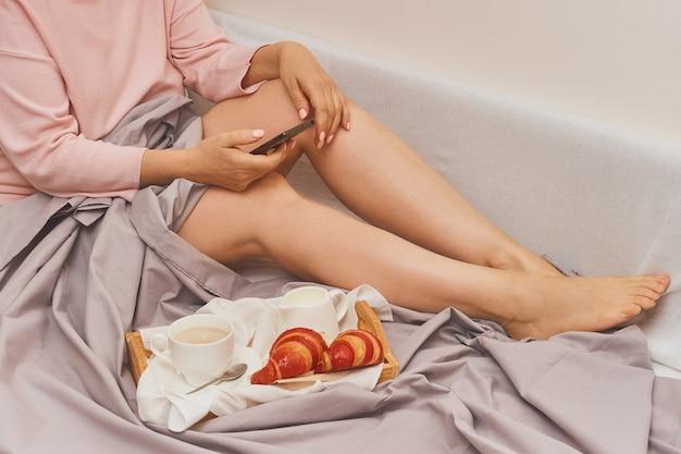 Kobieta w łóżku ze śniadaniem wpisując wiadomość w telefonie komórkowym