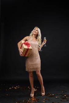 Kobieta w luksusowych sukienkach z okazji wigilii. złote balony i szampan