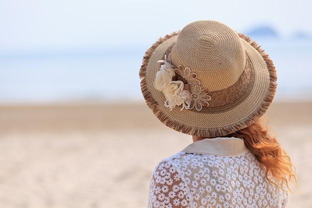 Kobieta w luksusowym kapeluszu patrząc na morze