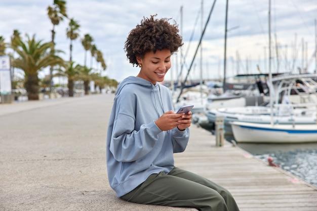 Kobieta w luźnych ciuchach siedzi na molo w porcie używa telefonu komórkowego sprawdza powiadomienia wysyła zdjęcia zamierza popłynąć luksusowym jachtem w porcie czyta sms-y