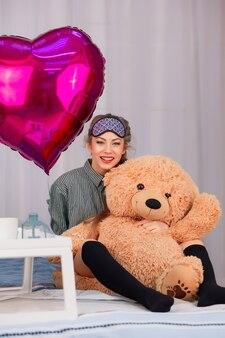 Kobieta w masce do spania uśmiecha się i przytula misia-zabawkę w walentynki obok różowego balonu