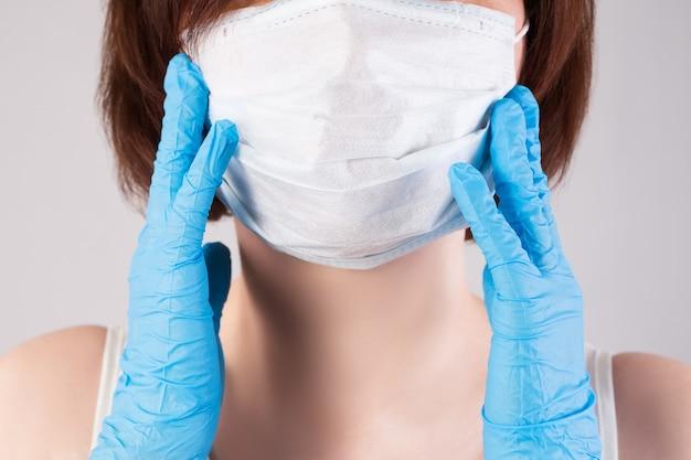 Kobieta w masce i rękawiczkach nitrylowych na szarej ścianie, wybuch koronawirusa 2019 lub covid-19