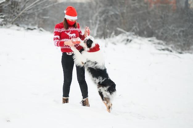 Kobieta w masce i świątecznym swetrze bawi się z australijskim pasterzem