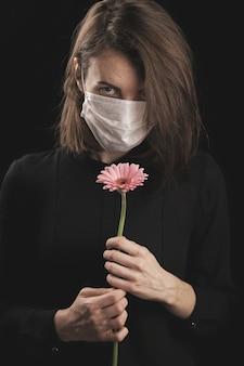 Kobieta w masce koronawirusa. piękna różowa stokrotka