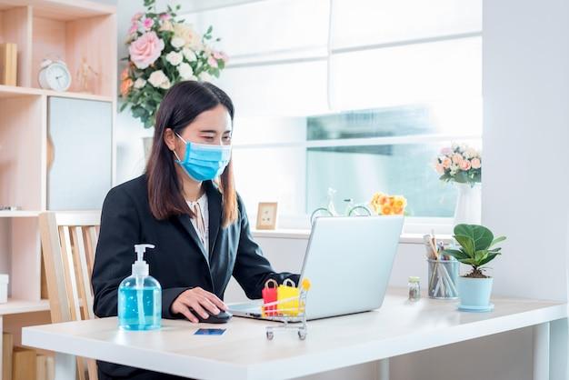 Kobieta w masce, która obecnie pracuje w domu i robi zakupy online w celu poddania się kwarantannie podczas wybuchu epidemii choroby koronawirusa (covid-19)