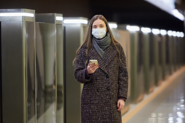 Kobieta w masce medycznej, aby uniknąć rozprzestrzeniania się koronawirusa, czeka na pociąg i trzyma telefon komórkowy na stacji metra