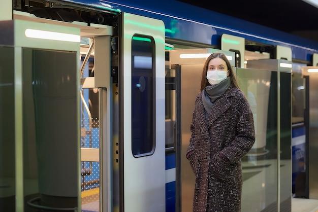 Kobieta w masce medycznej, aby uniknąć rozprzestrzeniania się koronawirusa, czeka w pobliżu nowoczesnego wagonu metra