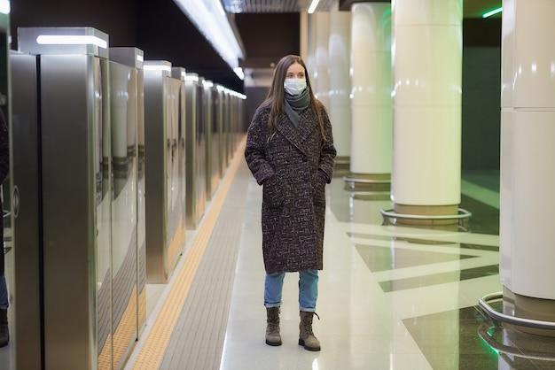 Kobieta w masce medycznej, aby uniknąć rozprzestrzeniania się koronawirusa, idzie, czekając na pociąg na peronie metra