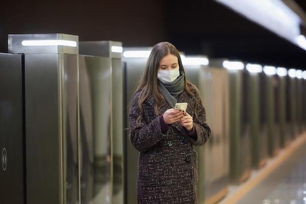 Kobieta w masce medycznej, aby uniknąć rozprzestrzeniania się koronawirusa, korzysta ze smartfona na platformie metra