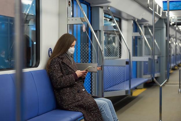 Kobieta w masce medycznej, aby uniknąć rozprzestrzeniania się koronawirusa, siedzi i używa smartfona w nowoczesnym wagonie metra