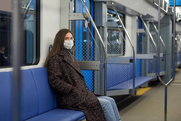Kobieta w masce medycznej, aby uniknąć rozprzestrzeniania się koronawirusa, siedzi samotnie w nowoczesnym wagonie metra