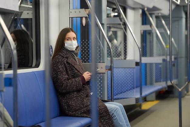 Kobieta w masce medycznej, aby uniknąć rozprzestrzeniania się koronawirusa, siedzi wpatrując się w bok w nowoczesnym wagonie metra