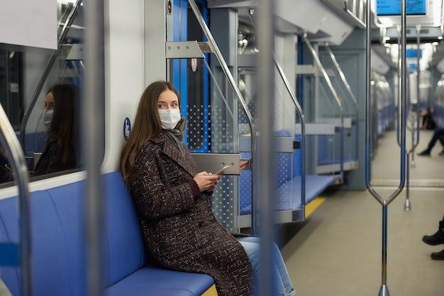 Kobieta w masce medycznej, aby uniknąć rozprzestrzeniania się koronawirusa, siedzi ze smartfonem w nowoczesnym wagonie metra