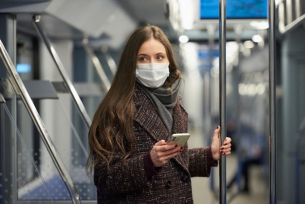 Kobieta w masce medycznej, aby uniknąć rozprzestrzeniania się koronawirusa, stoi i patrzy w bok w nowoczesnym wagonie metra