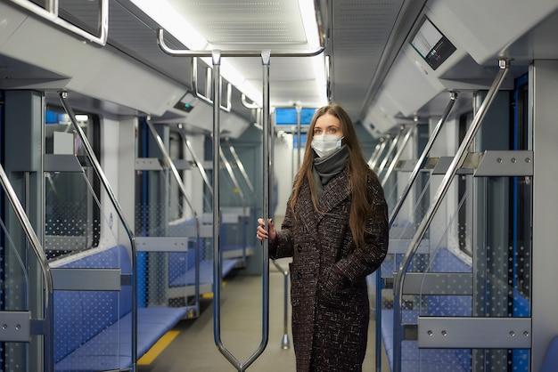 Kobieta w masce medycznej, aby uniknąć rozprzestrzeniania się koronawirusa, stoi i trzyma poręcz w nowoczesnym wagonie metra