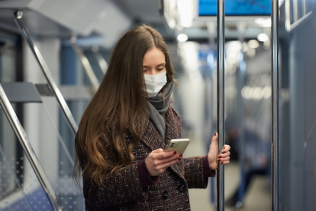 Kobieta w masce medycznej, aby uniknąć rozprzestrzeniania się koronawirusa, stoi i używa smartfona w nowoczesnym wagonie metra
