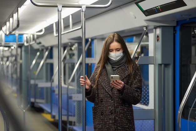 Kobieta w masce medycznej, aby uniknąć rozprzestrzeniania się koronawirusa, stoi i używa smartfona w pustym wagonie metra