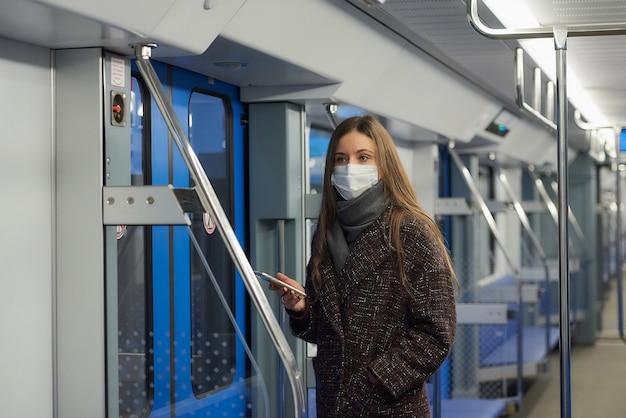 Kobieta w masce medycznej, aby uniknąć rozprzestrzeniania się koronawirusa, stoi w pobliżu drzwi i patrzy w bok w pustym wagonie metra