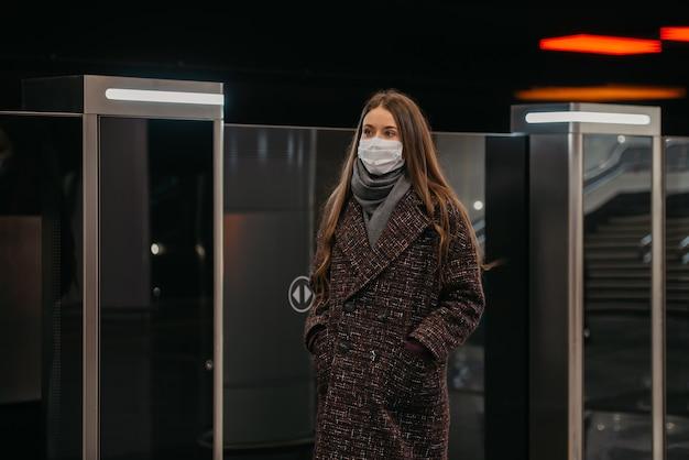 Kobieta w masce medycznej, aby uniknąć rozprzestrzeniania się koronawirusa, stoi w pobliżu odjeżdżającego pociągu na peronie metra. dziewczyna w masce chirurgicznej utrzymuje dystans społeczny na stacji metra.