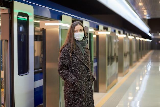 Kobieta w masce medycznej, aby uniknąć rozprzestrzeniania się koronawirusa, wysiada z nowoczesnego wagonu metra