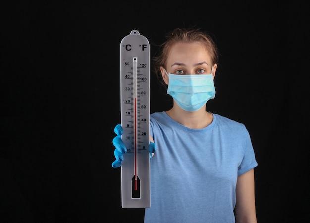 Kobieta w masce medycznej i rękawiczkach trzyma termometr pogodowy