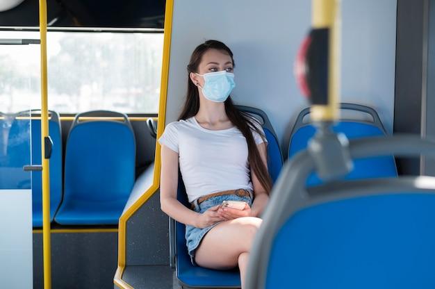 Kobieta w masce medycznej korzystająca z publicznego autobusu do transportu