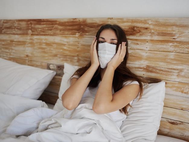 Kobieta w masce medycznej leży w łóżku na poduszce pandemiczna choroba płuc koronawirusa kwarantanny