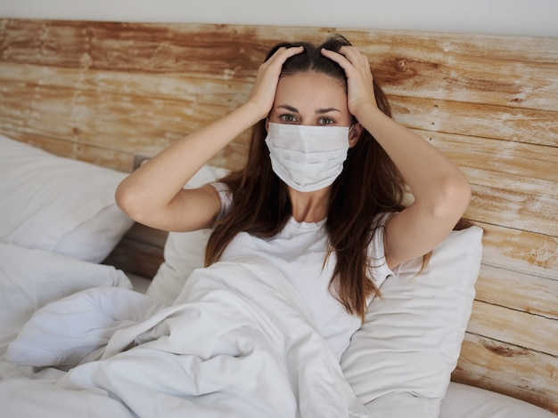 Kobieta w masce medycznej leży w łóżku pod kołdrą i dotyka rękami głowy