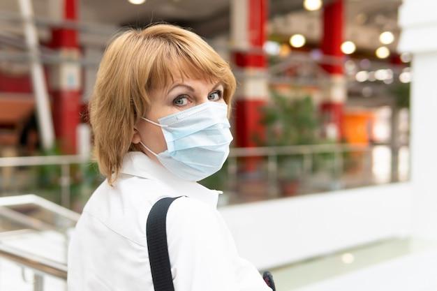 Kobieta w masce medycznej na koronawirusa spaceruje po centrum handlowym w mieście. boi się covid-19